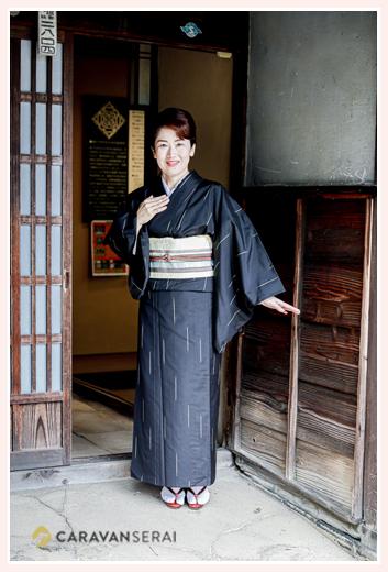 黒の大島紬の着物を着る女性