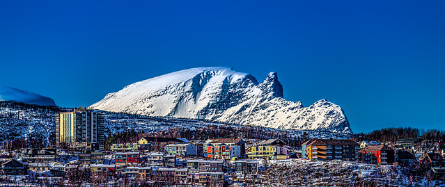 Houses and apartments on a hillside with a jagged rock formation in the background at Narvik, Norway-59a