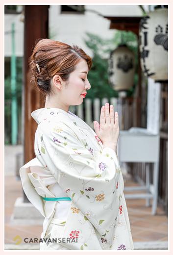 神社で手を合わせて祈る女性 白い着物