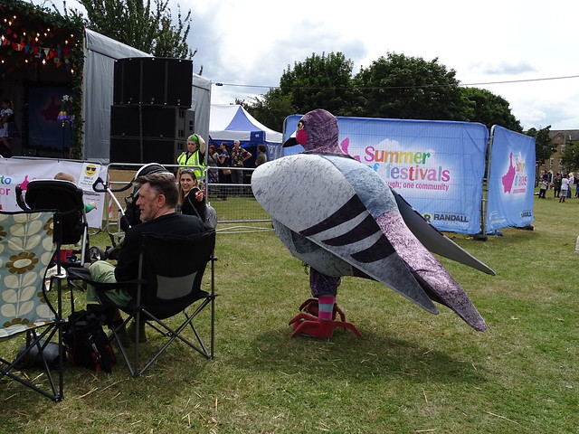 PEOPLE SITTING ENJOYING THE COMPANY OF A LARGE PIGEON IN AN EAST LONDON BOROUGH SUBURB STREET PARK EVENT VENUE ENGLAND DSC02230