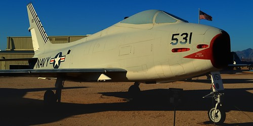 nikond3200 edk7 2013 usa arizona tucson arizonaaerospacefoundation pimaairspacemuseum unitedstatesnavy usn northamericanaviation northamericanaf1efury sn139531 1956 prototype aircraft airplane plane aviation military jet fighterbomber nuclearstrike usnprototypeflighttestingcolumbusnavalairstationnas1956 wrightj65w16turbojet7700lbf oldglory flag hangar gravel sky mountain shadow sunset