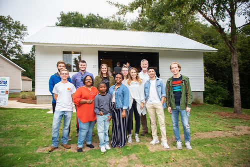Auburn University students stand with the Dumas family in front of the Habitat for Humanity house.