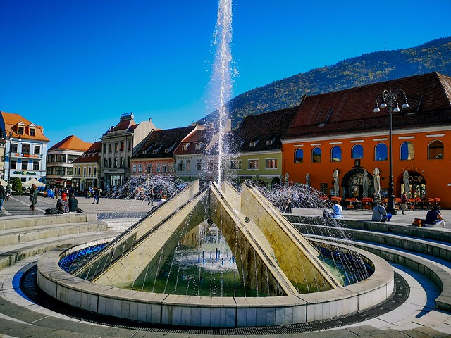 City center fountain in Brasov, Romania with circular formed seats around.
