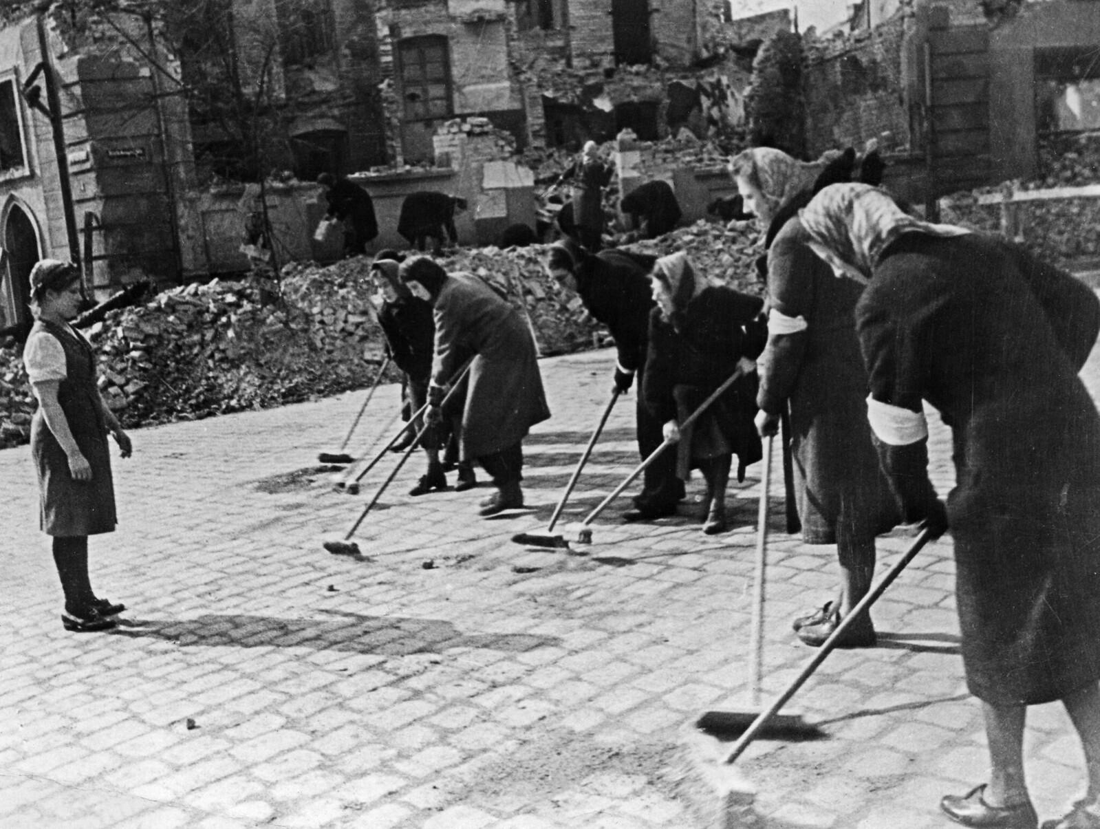 1945. Немецкие женщины, подметающие улицу Берлина после капитуляции под присмотром Маруси Кузнецовой, которая более двух лет провела в качестве подневольной работницы в Германии