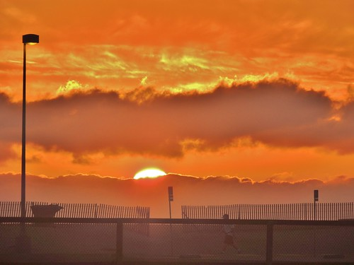 nikon janelazarz orange huntingtonbeachca sunset clouds sunsetbeachca fence beach jogging jogger