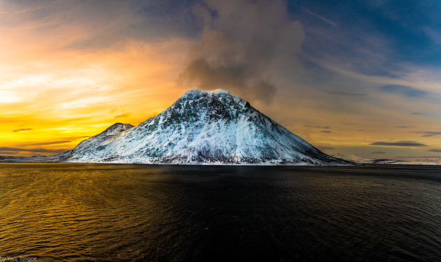 Multiphoto panoramic view of sunrise behind the mountain on Kågen island, Norway while sailing between Arnøya and Kågen Islands-9