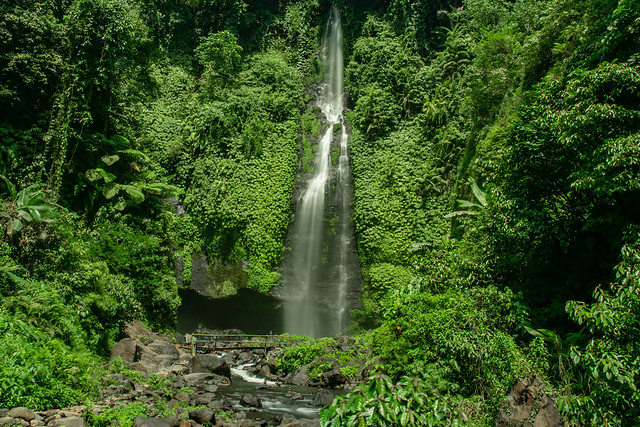Beautiful tall waterfall cascading out of the lush green tropical jungle