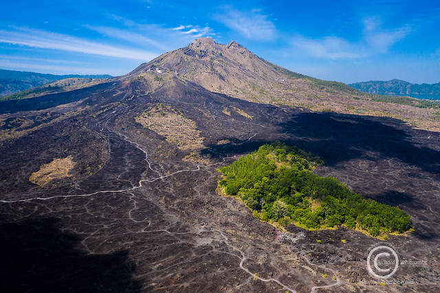 Black lava flows around the active volcano Mount Batur in Bali, Indonesia