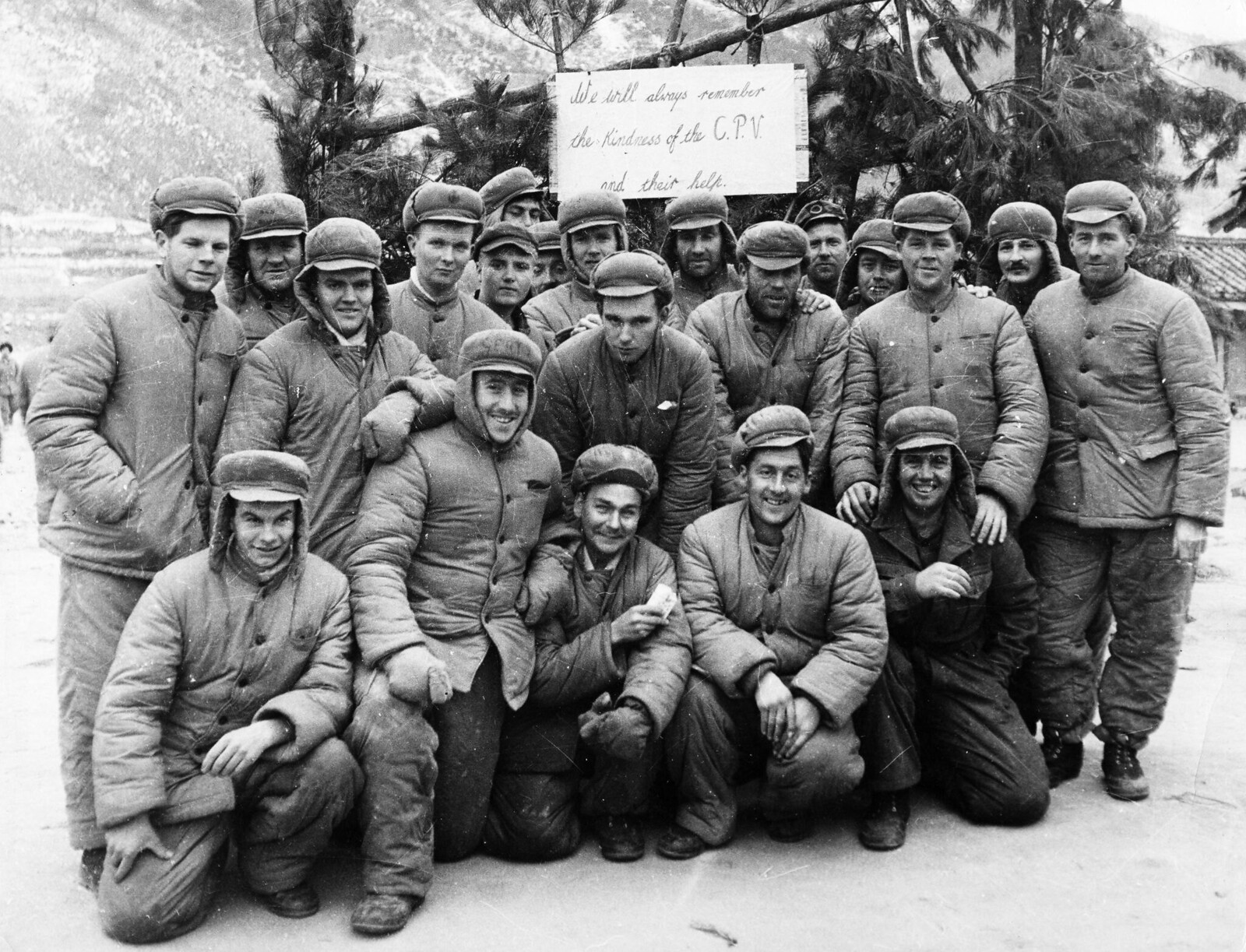 1953. Корейская война. Счастливая группа американских заключенных в северокорейском лагере для военнопленных. Знак позади них гласит «Мы всегда будем помнить о доброте КНД (китайских народных добровольцев) и их помощи».