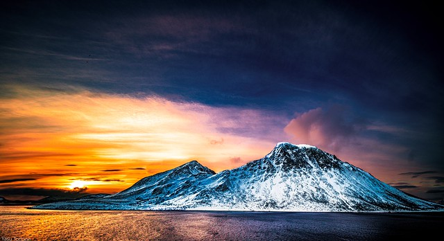 View of sunrise behind the mountain on Kågen island, Norway while sailing between Arnøya and Kågen Islands-14a