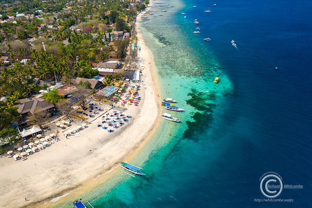 Aerial view of outrigger boats on the coral reef surrounding Gili Air in Lombok, Indonesia