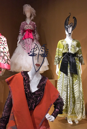 Photo of three dresses on mannequins, two of which are wearing masks