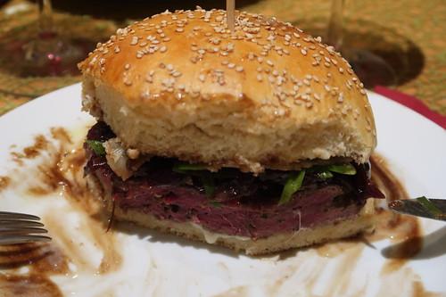 Burger mit selbstgebackenen Sesam-Buns, frisch angerührter Walnussöl-Honig-Senf-Mayonnaise, Balsamico-Zwiebeln, Parmesan und Patties aus Hirschfilet (angeschnitten)