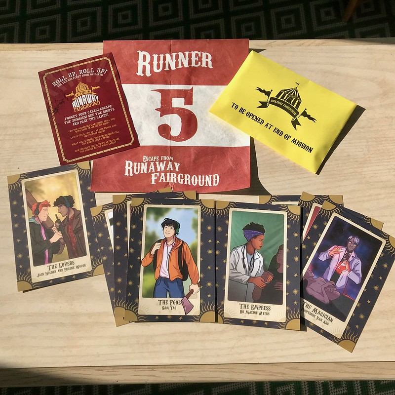 Race packet contents on a table, including tarot cards with character portraits