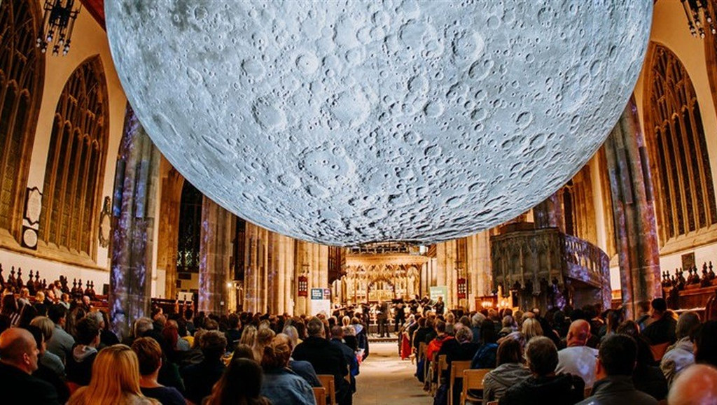Artwork of a moon hanging from the ceiling of a cathedral with visitors looking up at it