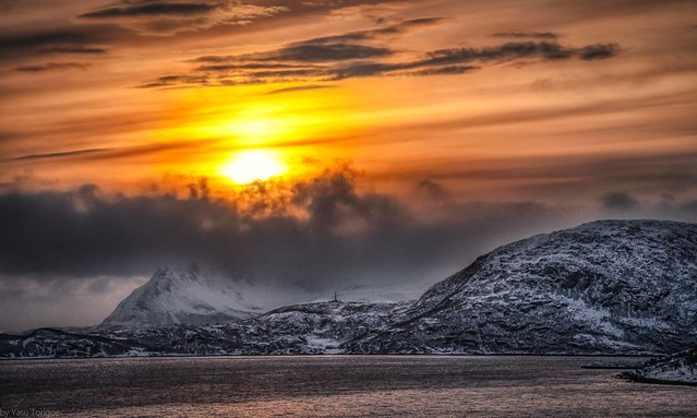 View of sunrise behind the mountain on Kågen island, Norway while sailing between Arnøya and Kågen Islands-16a