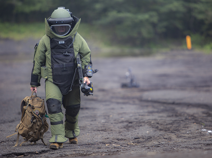 A man in protective gear walks with a backpack in his right hand.