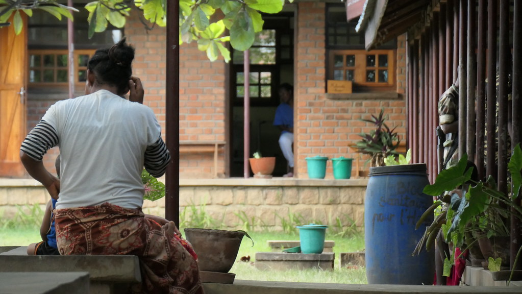 Malagasy woman sits outside hospital.