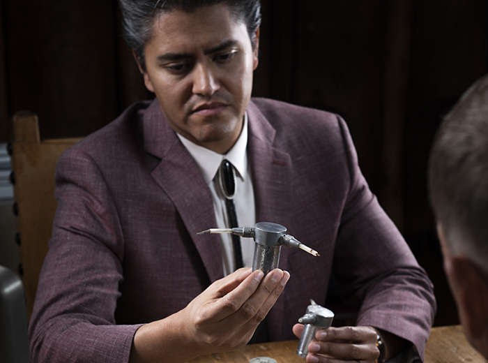 A man in a suit looks at two exploding-bridgewire detonators; he's holding one detonator in each hand.