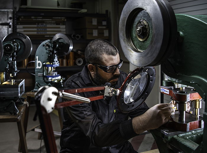 A man wearing safety glasses holds something small in his hands and works on it using a piece of equipment.