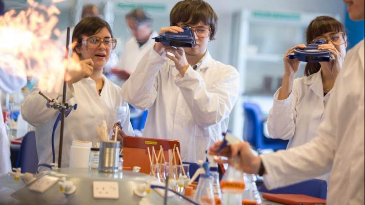 Students dressed in white lab coats in a lab taking part in chemistry experiments