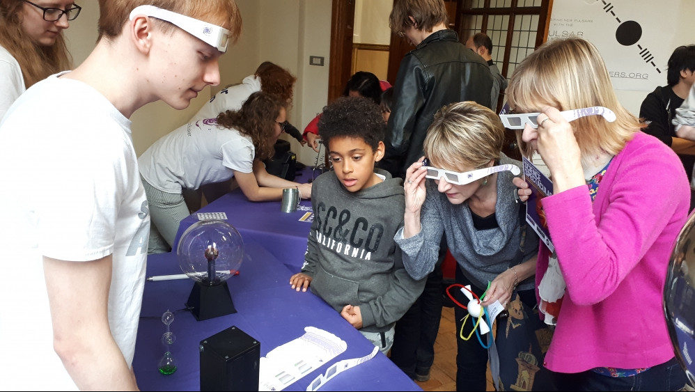 Two young children talking to a mathematician at a science festival