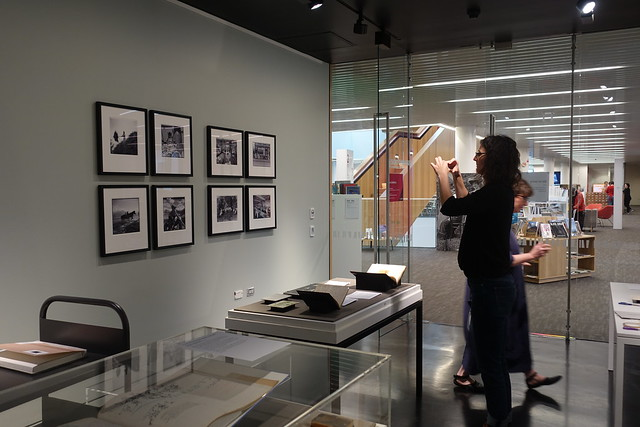 Curator snapping a photo during installation