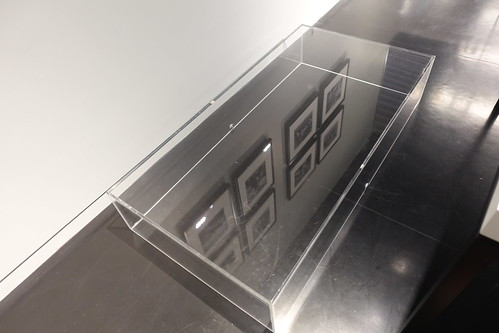 Photographs reflected in display case lid
