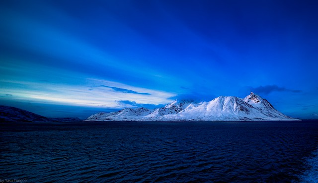 View of sunrise behind the mountain on Kågen island, Norway while sailing between Arnøya and Kågen Islands-22a
