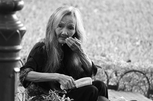 Señora peinando sus cabellos  vividos, se ve claramente el paso del tiempo sobre su rostro, sobre su piel, con una mirada limpia, dulce e inocente, como un niño, expectante y tranquilo. Toda una belleza. Hanoi, Vietnam.