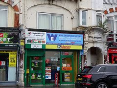 "A mid-terrace ground-floor shopfront with a sign reading ""Afghan Exchange & Travel Ltd"" over the left third and another reading ""Worf Enterprises Shipping"" over the remaining two-thirds.  The fully-glazed frontage is part-covered with posters for various money-transfer services, and large shipping containers can be seen inside.  An arched recessed doorway to the right of the shop has the name ""Royal Mansions"" embossed above it."