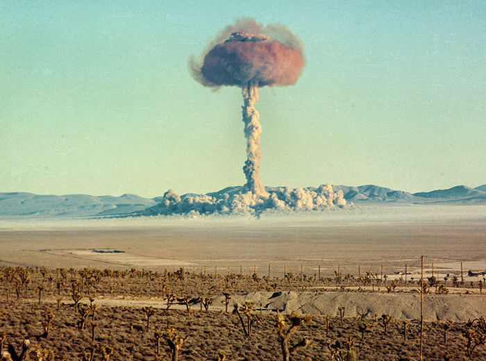 A mushroom cloud rising above the desert.