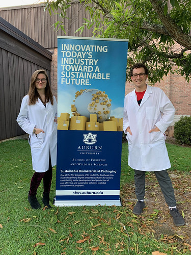 """Autumn Reynolds and Philip McMichael stand next to a sign that reads """"Innovating Today's Industry Toward A Sustainable Future."""""""