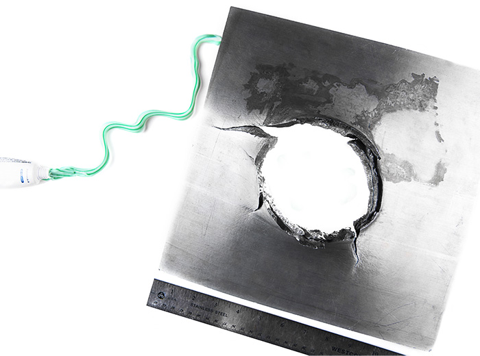 A metal blast plate with a hole in the middle of it. To the left is a tube of toothpaste, and there is a line of green-and-white toothpaste going from the toothpaste tube to the blast plate.