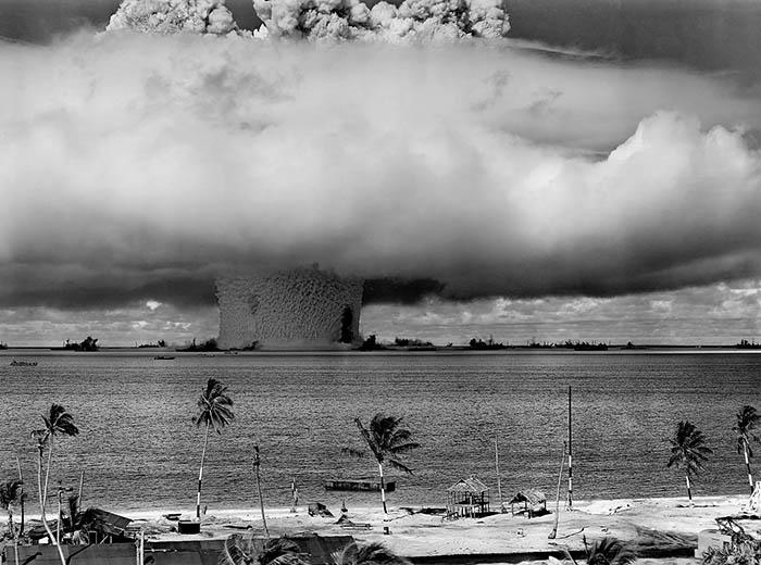 A mushroom cloud rises out of the ocean near a beach with palm trees.