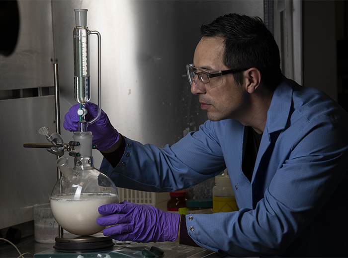 A chemist in a blue lab coat works with liquid in a round beaker.