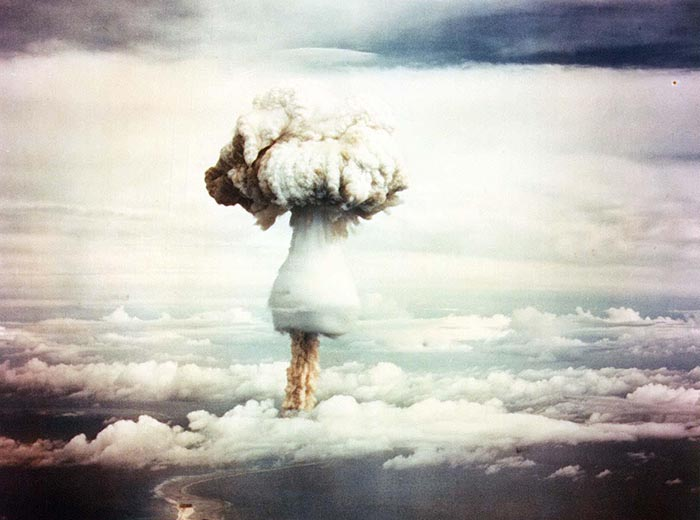 A mushroom cloud with a skirt-like at the bottom rising above clouds.