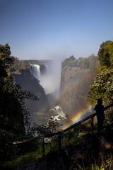 admiring the double rainbow, on the steps at Victoria Falls or Mosi-oa-Tunya (The Smoke that Thunders), Zambezi River, Zambia, Zimbabwe, Africa