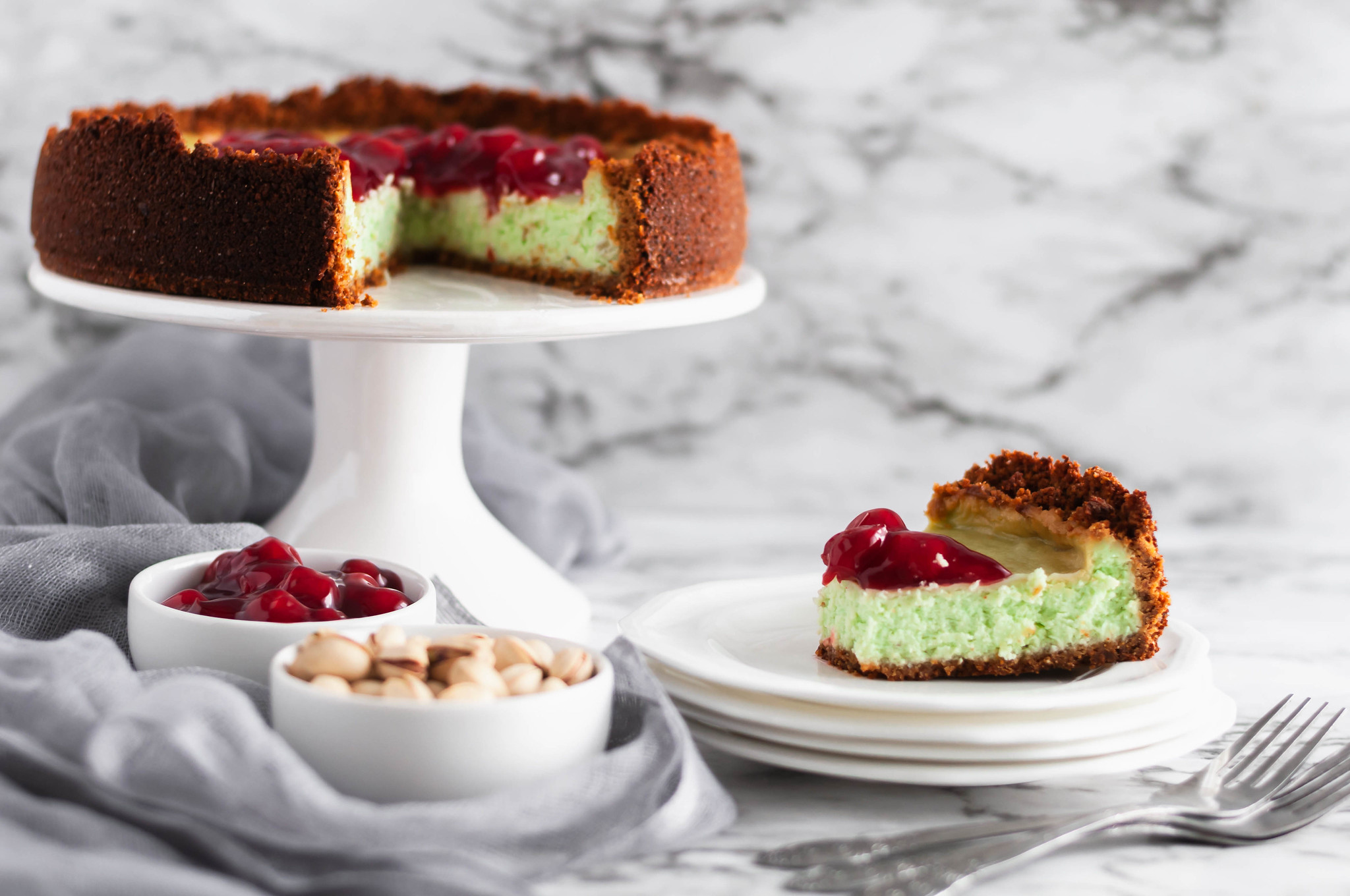 This PIstachio Cheesecake is a delightful holiday dessert. Thick, creamy cheesecake studded with pistachio flavor throughout the filling and crust. Top with cherries to make it extra festive.