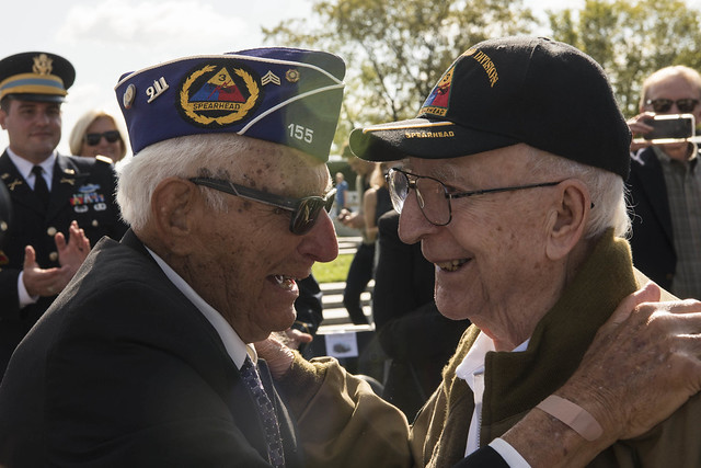 WWII veterans embracing each other during the WWII Bronze Star Award Ceremony at the National WWII Memorial