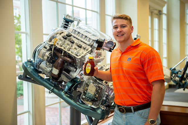 Eddie Strickland holds a jar of honey in front of an engine in Auburn's mechanical engineering building.