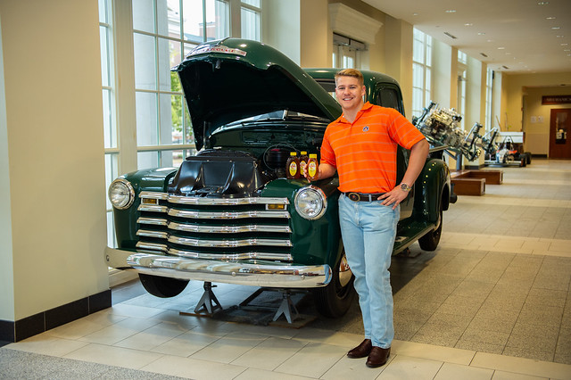 Eddie Strickland holds a jar of honey as he stands near a truck in Auburn's mechanical engineering building.