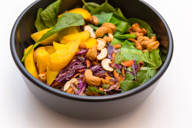 Indian Summer Bowl with leaf spinach, sugar peas, warm rosemary potatoes, raw vegetable salad, roasted yellow carrots, cashews, basil, coriander and yellow Thai curry sauce