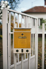 A yellow mailbox with the iron grill door.