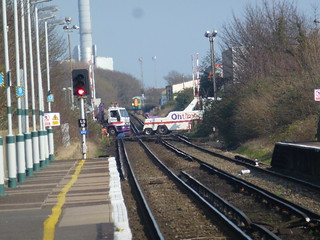 Broken down truck on the level crossing about to be towed by the same company