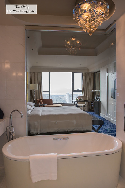 Bathroom with a glass wall to view the bed room and window to West Lake