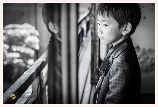 窓から庭を眺める男の子 モノクロ写真