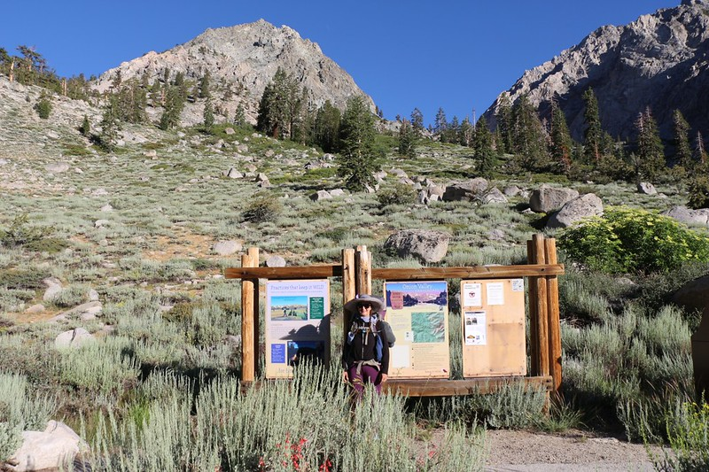 Vicki at the Kearsarge Pass Trail trailhead sign in Onion Valley - ready to trek to Rae Lakes for seven days