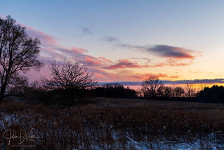 An early winter snow storm clears revealing whispy cloud formations, painted in pastel colors by the sunset.  Lakewood forest preserve.