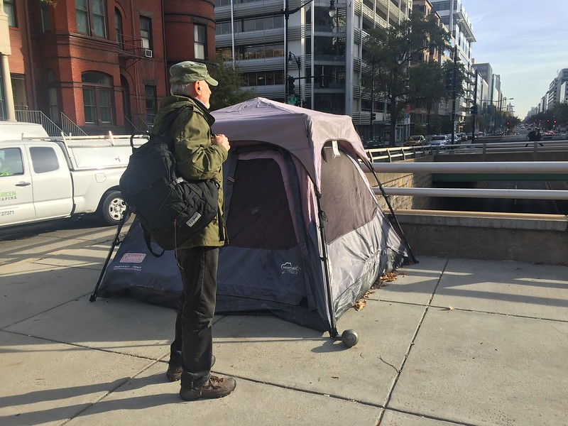 Photo of a man in green with a backpack next to a tent pitched on a sidewalk on an overpass.